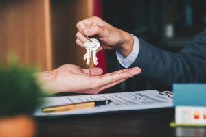 real estate agent handing the house key to the new home owner
