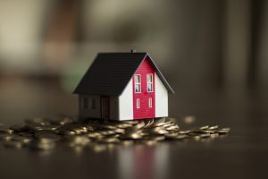 miniature home placed above a stack of coins